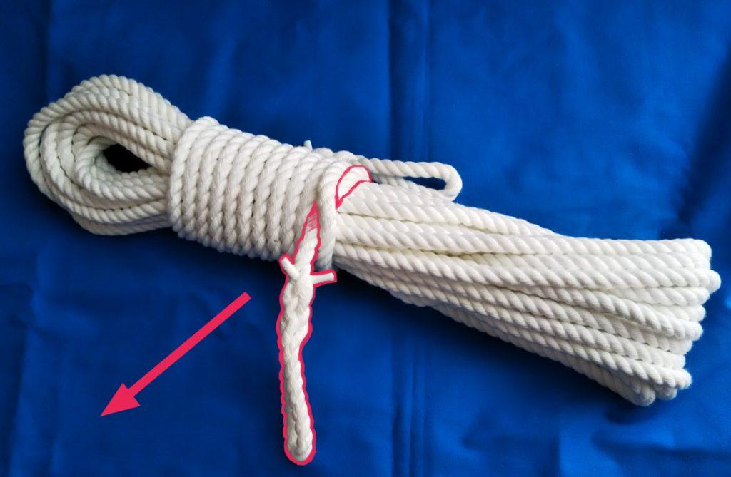 青い布の上に束ねられたロープが置いてある。棒結び