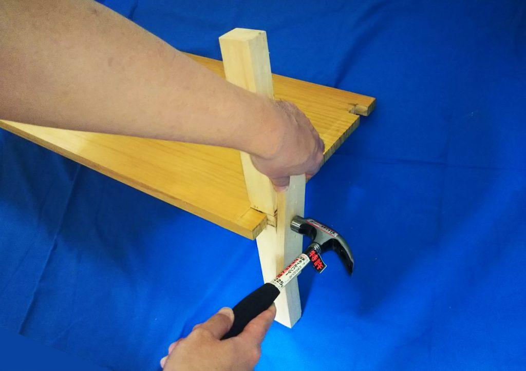 当て木を添えて十字相欠き継ぎ加工をした角材をはめ込んでいくところ